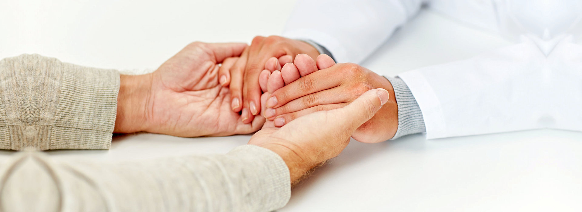 Caregiver is holding the hands of the patient